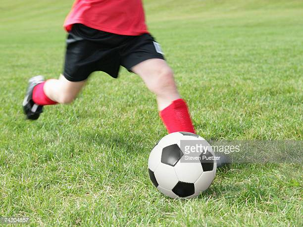 Boy (6-7 years) running and kicking soccer ball on grass, low section