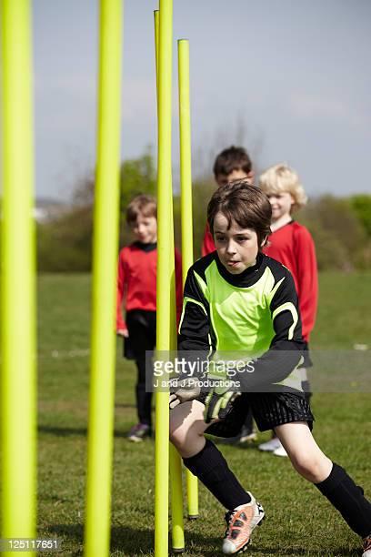 Boy running around training poles