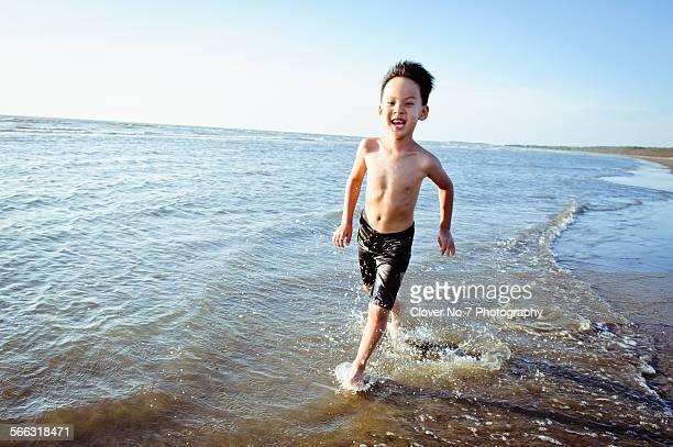 boy running at the beach. - knaben in badehosen stock-fotos und bilder
