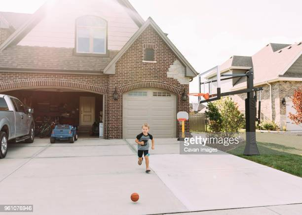 boy running behind basketball on driveway - driveway stock pictures, royalty-free photos & images