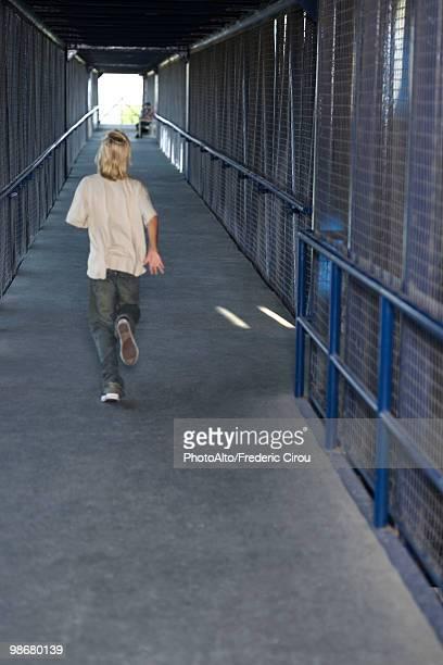Boy running down corridor, rear view