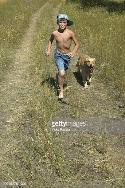 Boy (10-12) running in field with Golden Retriever, portrait