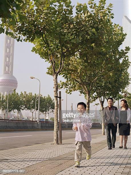 Boy (4-6) running in front of parents on sidewalk