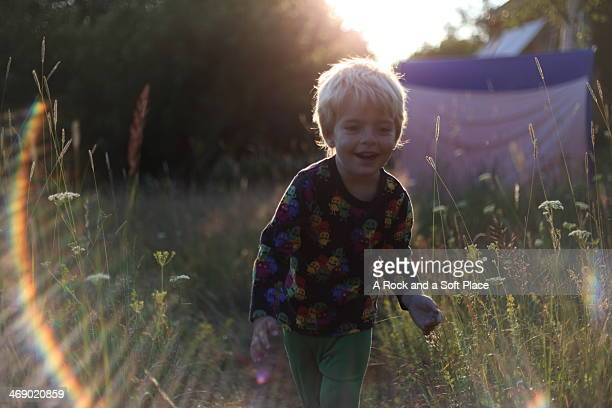Boy running in high grass, with lens flare
