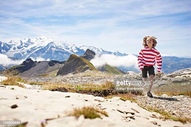 Boy running in rocky landscape