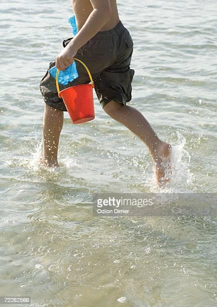 Boy running in surf at beach