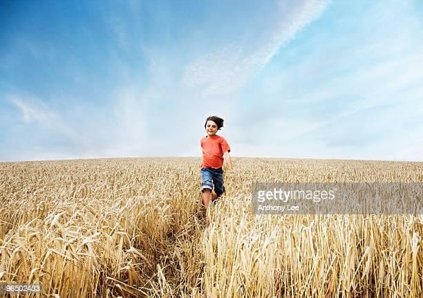 Boy running in wheat field