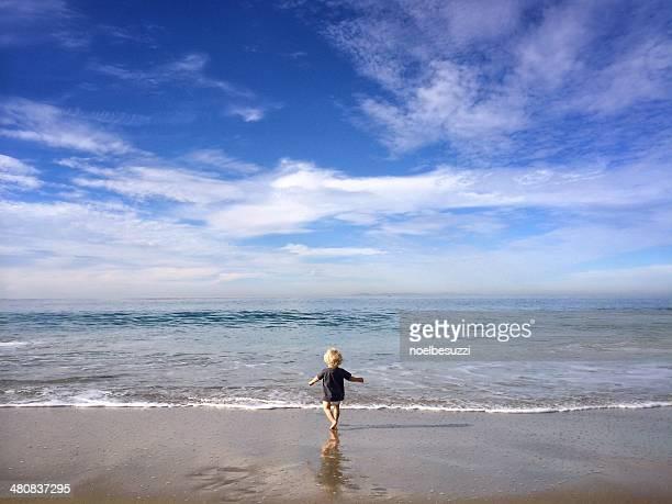 Boy running into the ocean, California, America, USA