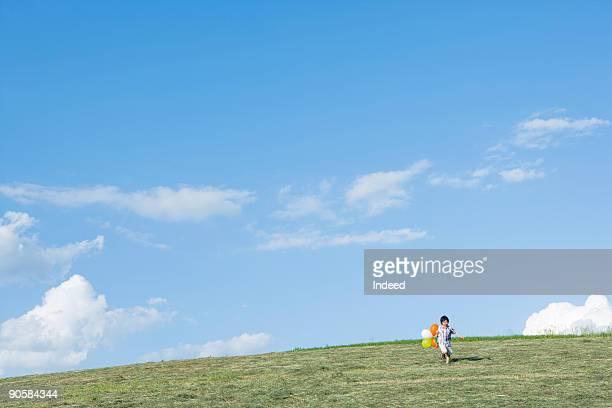 boy (6-7) running on field, holding balloon - 丘 ストックフォトと画像