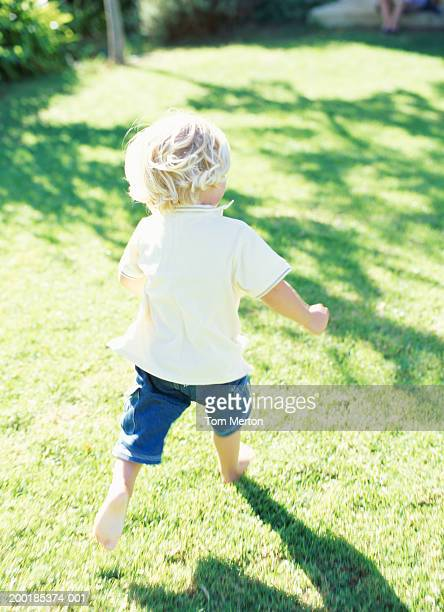 Boy (2-4) running on grass with bare feet, rear view