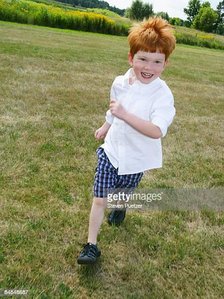 Boy running on green grass