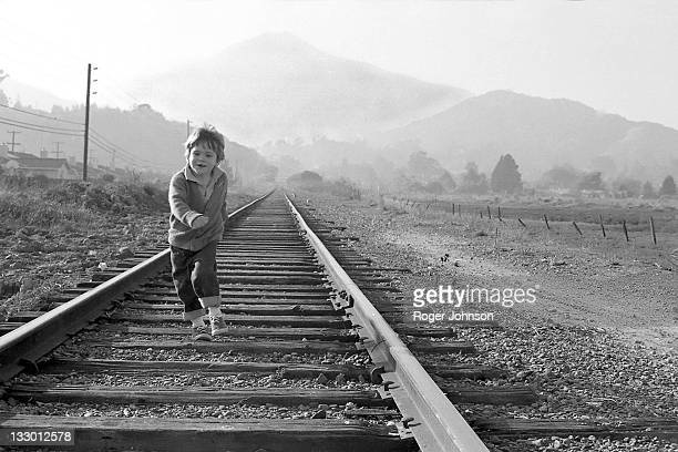 Boy running on railroad tracks