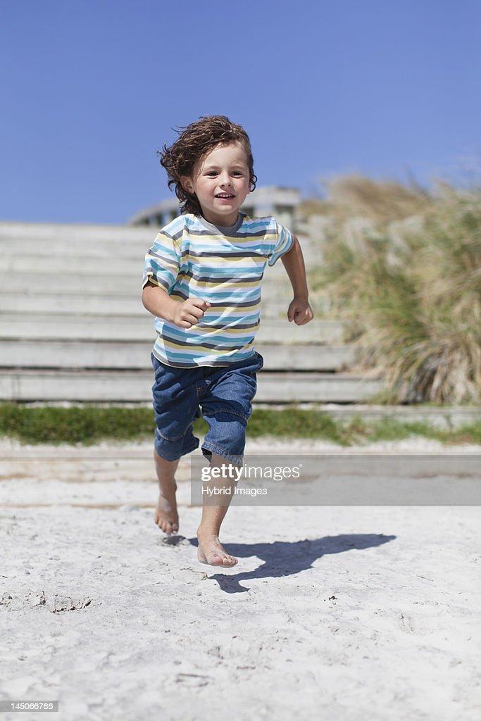 Boy running on sandy beach : Stock Photo