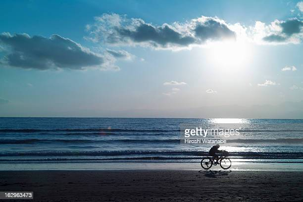 Boy running on the beach by bicycle