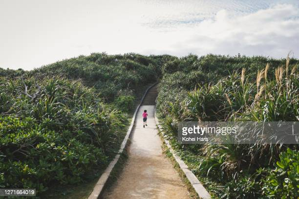 boy running on the straight road in the mountain - okinawa prefecture stock pictures, royalty-free photos & images