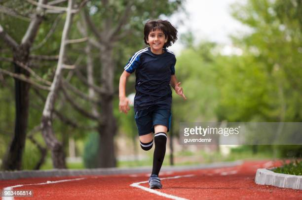 boy running on track - athleticism stock pictures, royalty-free photos & images
