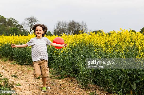 Boy running on yellow flower field track pulling red balloon