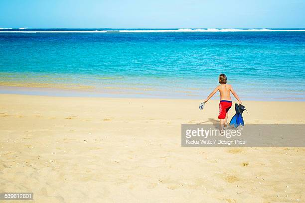 A boy running out to the ocean across the beach with snorkelling gear
