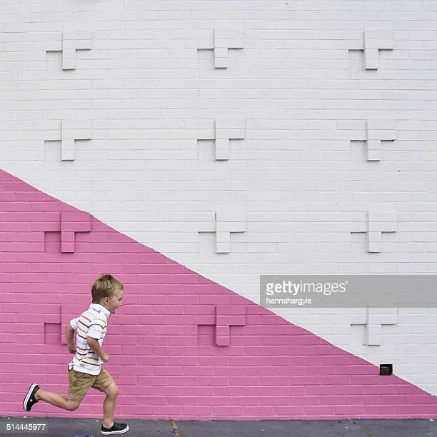 Boy running past pink and white wall
