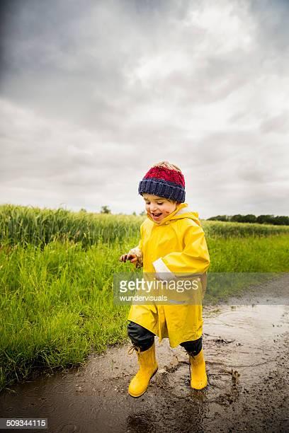 Junge Laufen durch Big Pfütze