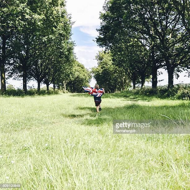 Boy running through field holding Union Jack flag