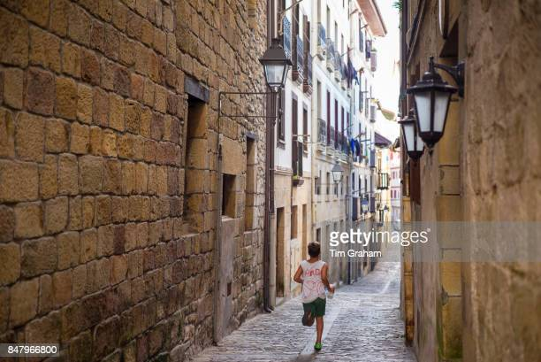 Boy running through the alleyways of old town Hondarribia in Basque Country Spain