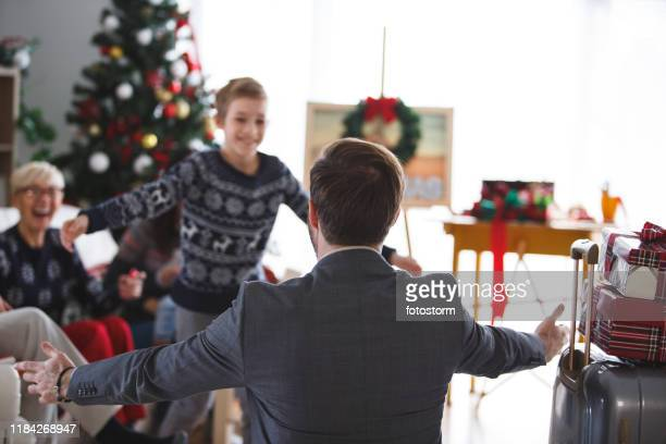 boy running to his dad after he gets home from work - hello december stock pictures, royalty-free photos & images