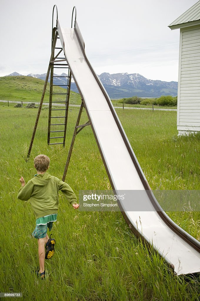 Boy running to slide : Stock Photo