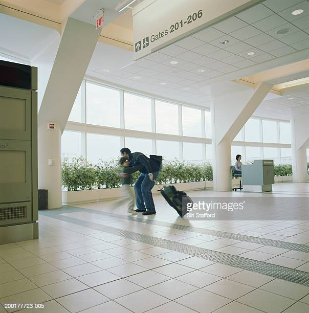 Boy (6-8) running to welcome father in airport