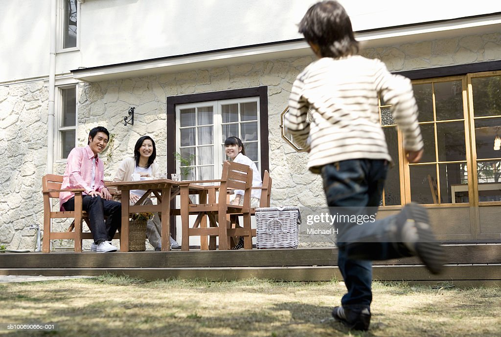 Boy (6-7) running towards family sitting outside house (blurred motion) : Stockfoto