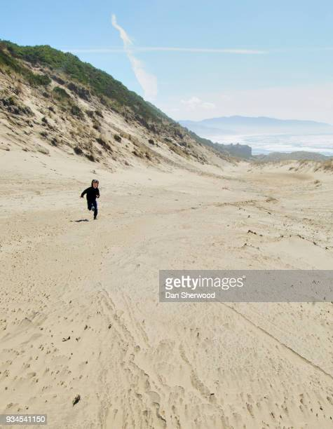 Boy Running Up a Sand Dune at the Beach at Cape Kiwanda - Oregon