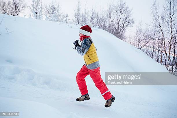Boy running up snow covered hill, Hemavan,Sweden