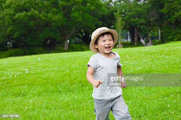 Boy running while merrily laughs a park