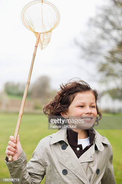 Boy running with a butterfly net in a park