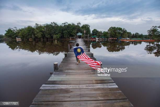 een jongen die met een lange maleisische vlag op een pijler / pier loopt - maleisië stockfoto's en -beelden