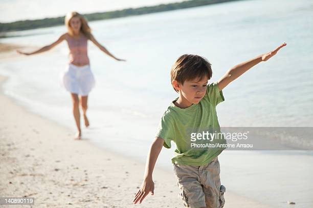 Boy running with arms out at the beach