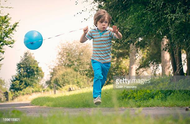 Boy running with balloon outdoors