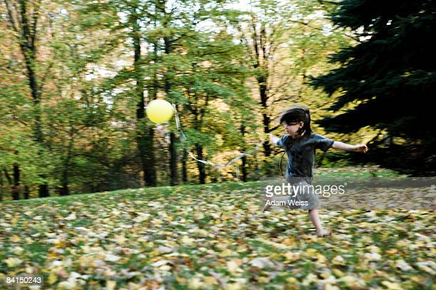 Boy running with balloon