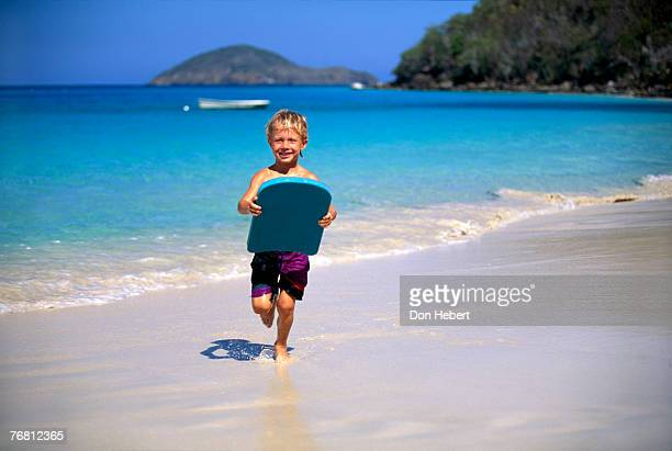 Boy running with body board on beach