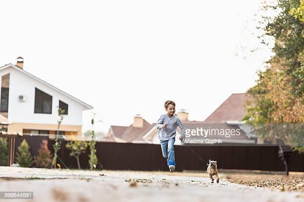 Boy running with dog on footpath against clear sky
