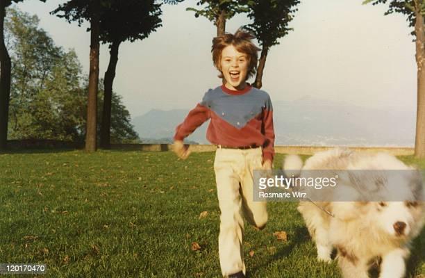 boy running with dog - di archivio foto e immagini stock
