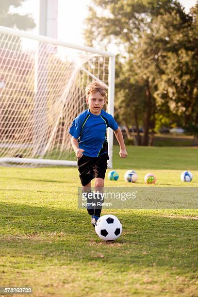 Boy running with football on practice pitch