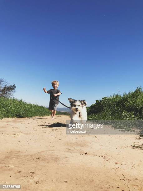 Boy running with his puppy dog in the park, Orange County, California, America, USA