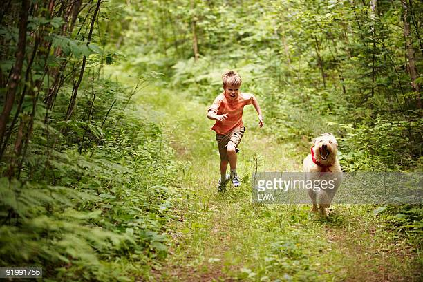 Boy Running With Labradoodle