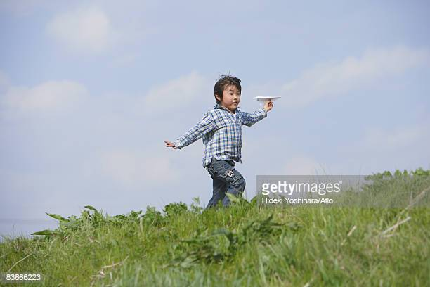 Boy running with paper airplane in park