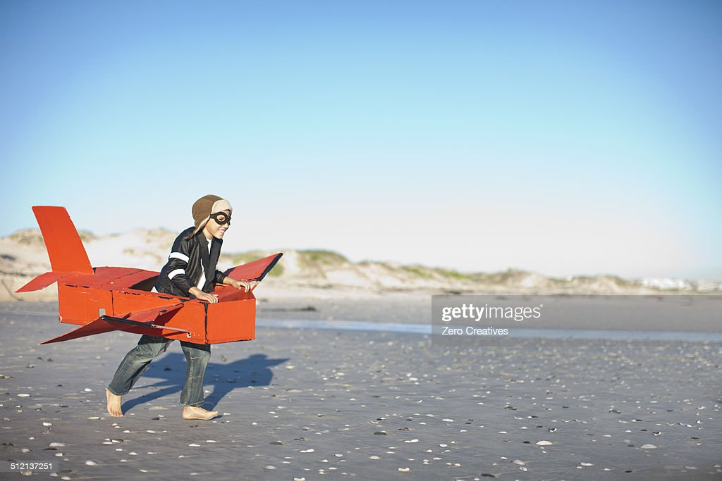 Boy running with toy airplane on beach : Stock Photo