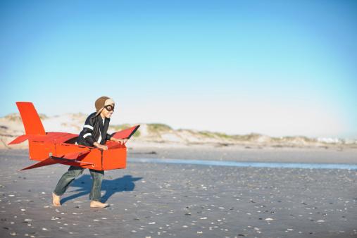 Boy running with toy airplane on beach - gettyimageskorea
