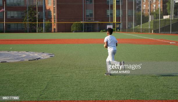 A boy runs after a ball during baseball practice at the Nationals Youth Baseball Academy in Washington DC on May 7 2018 On a searing hot summer's day...