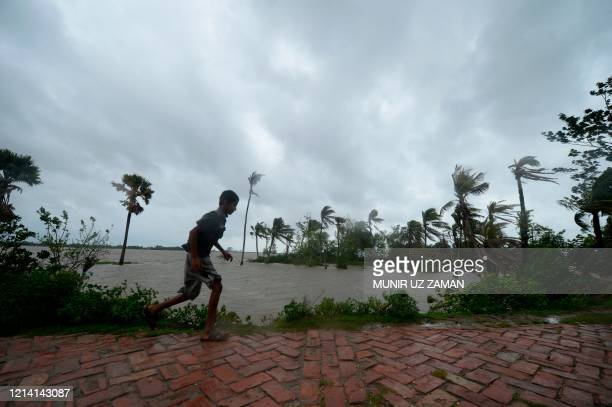 TOPSHOT A boy runs along an embankment ahead of the expected landfall of cyclone Amphan in Dacope on May 20 2020 Several million people were taking...