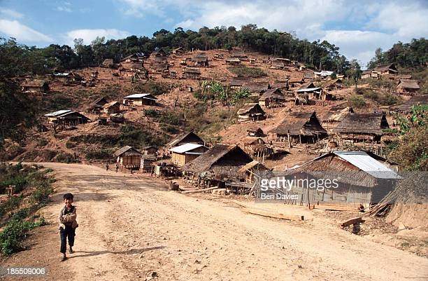 A boy runs along the dirt road at the hilltribe village of Lao Huay situated to the north of Oudomxai in Laos The settlement is made up of thatched...